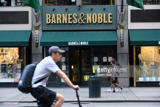 People walk outside the Barnes & Noble book store on Fifth Avenue as New York City moves into Phase 2 of re-opening following restrictions imposed to...