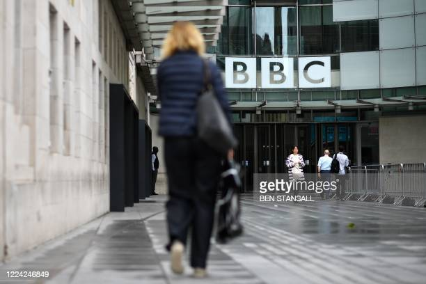 People walk outside the BBC headquarters in Portland Place, London on July 2, 2020. - The BBC announced on Thursday its intention to cut 450 jobs in...