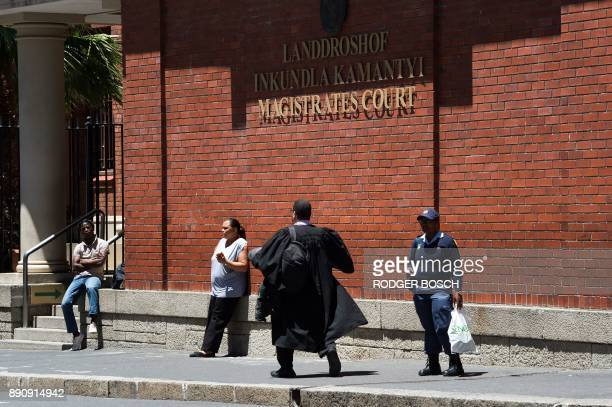 People walk outside the Cape Town Magistrate's court where the bail application of a Dutch convicted arms dealer is being heard on December 12 2017...