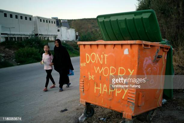 People walk outside the Moria migrant camp which was built for 3000 people but now contains over 13000 on October 09 2019 in Mytilene Greece...