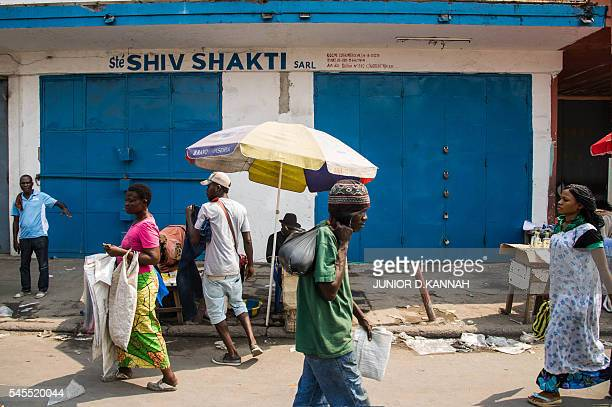 People walk outside the shut doors of a shop owned by businessmen of Indian origins in the Grand Marche Central district in Kinshasa on July 8 2016...