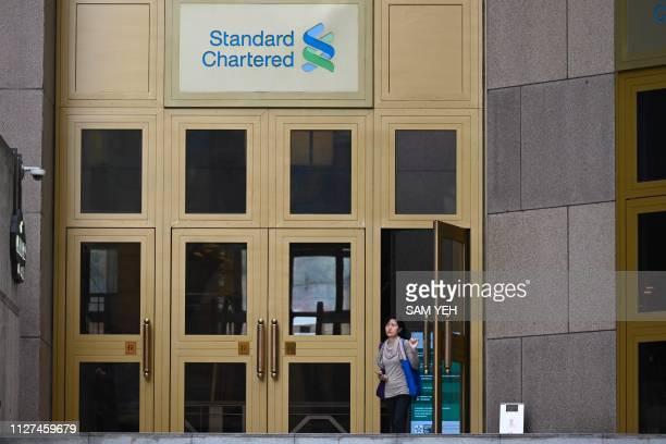 People walk outside the Standard Chartered Bank headquarters in Hong Kong on February 26 2019 Standard Chartered's fortunes climbed in 2018 to 39...