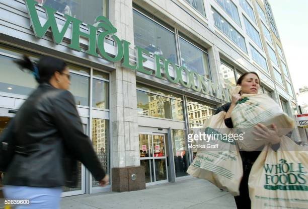 People walk outside the Wholefoods Market in Union Square April 16 2005 in New York City A growing group of shoppers are willing to spend more on...