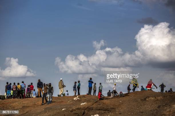 People walk over a mound on October 28, 2017 in the Mathare slums of Nairobi, a stronghold of Kenyan opposition leader. - Kenya was stuck in limbo on...