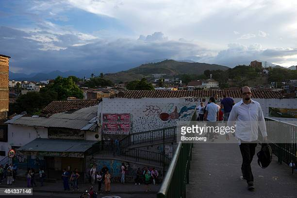 People walk over a pedestrian bridge in Cali Colombia on Wednesday Aug 12 2015 Colombia's central bank last month cut its forecast for 2015 economic...