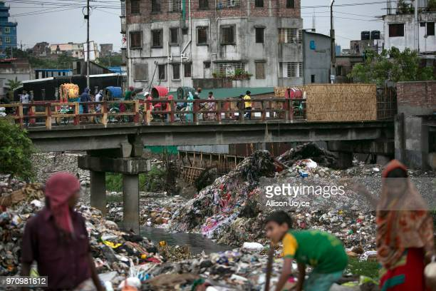 People walk over a polluted canal that leads to the Buriganga river June 10 2018 in Dhaka Bangladesh Bangladesh has been reportedly ranked 10th out...