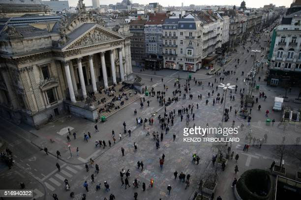 People walk over messages written on the ground at a makeshift memorial at Place de la Bourse following attacks in Brussels on March 22 2016 Airlines...