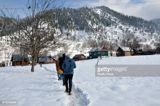 People walk over snow covered path after fresh snowfall in Daksum about 97 kilometers south of Srinagar city the summer capital of Indiancontrolled...