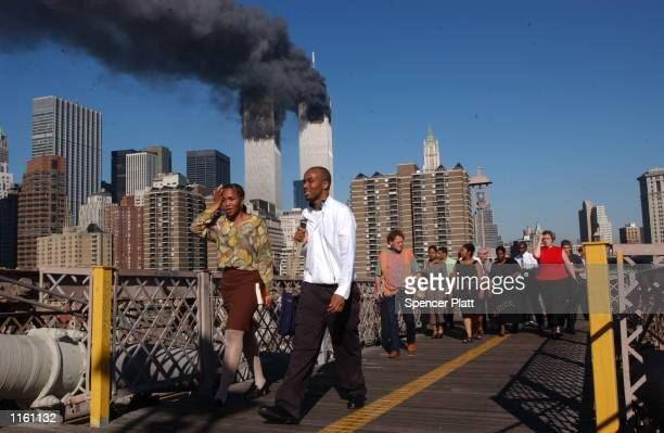 People walk over the Brooklyn Bridge as the world trade center burns September 11 2001 after two hijacked airplanes slammed into the twin towers in...