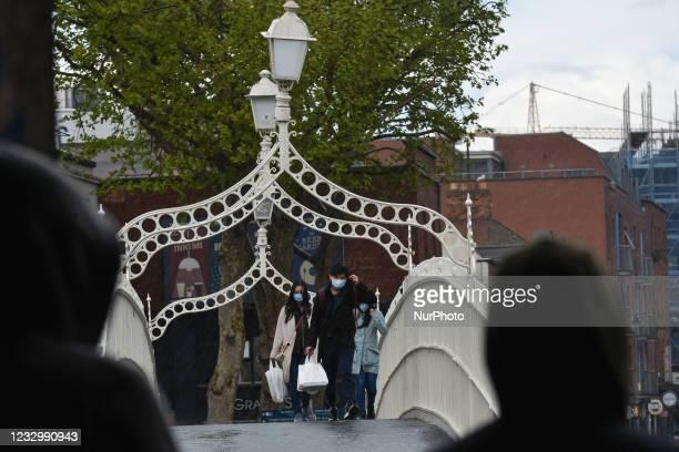 People walk over the Ha'Penny Bridge in Dublin city center during the rain On Tuesday, 18 May 2021, in Dublin, Ireland.
