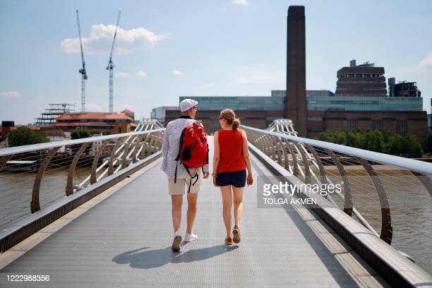 People walk over The Millennium Bridge towards Tate Modern in London on June 26 as temperatures are expected to again be high, hitting 31 degrees...