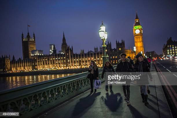 People walk over Westminster Bridge near the Houses of Parliament on October 26 2015 in London England The House of Lords will vote today on a motion...