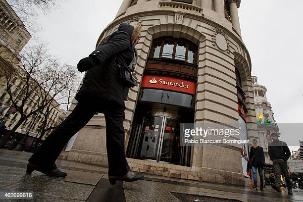 People walk pass a Banco Santander's office on February 2 2015 in Madrid Spain The eurozone's largest bank announced profits rose in all its 10 key...