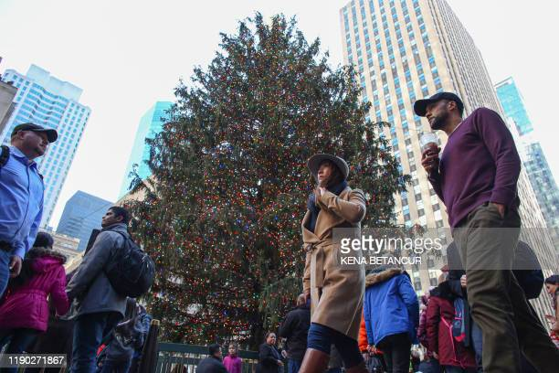 People walk pass by the Christmas tree at Rockefeller center on December 23, 2019 in New York City.