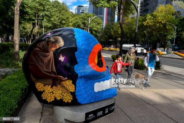People walk pass next to a colorful skull painted by Axolotl Collective and titled 'El Ciclo Infinito' at Reforma avenue in Mexico City on October 23...