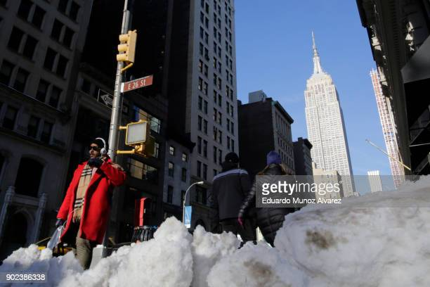 People walk pass snow accumulated on the sidewalk during freezing temperatures on January 07 2018 in New York city New York Much of the United...