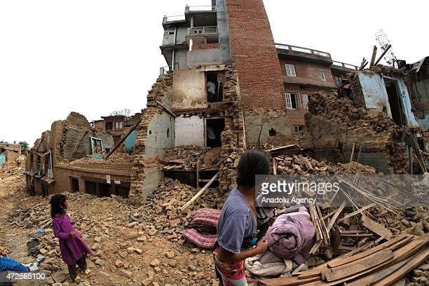 People walk pass the debris of a destroyed house at Dharmasthali in Kathmandu on May 8 after the devastating 78magnitude earthquake struck Nepal on...