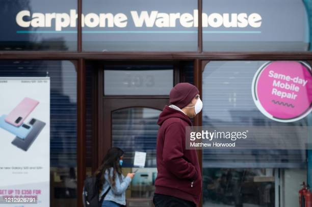 People walk passed a Carphone Warehouse store in central Cardiff wearing surgical masks on March 17 2020 in Cardiff Wales The phone retailer has...