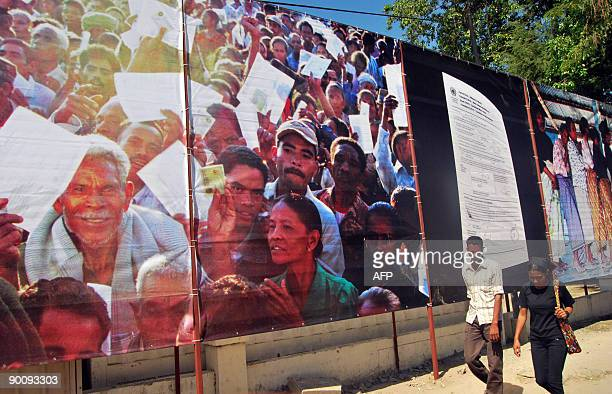 People walk passing a picture featuring the referendum on August 30 as part of preparations for the 10th anniversary of independence in Dili on...