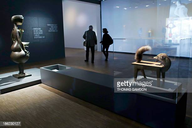 People walk past a 1947 work of art entitled 'Louptable' by Romanian artist Victor Brauner displayed during the exhibition Le surrealisme et l'objet...