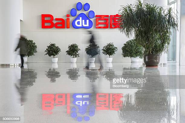 People walk past a Baidu Inc logo displayed in the reception area of the company's headquarters in Beijing China on Tuesday Jan 19 2016 Wang Jing the...
