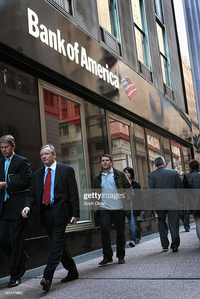 People walk past a Bank of America branch in the Financial District on November 1, 2011 in Chicago, Illinois. Bank of America Corp. has reportedly announced they will drop its plan to charge customers a $5-per-month fee for making purchases with their debit cards.
