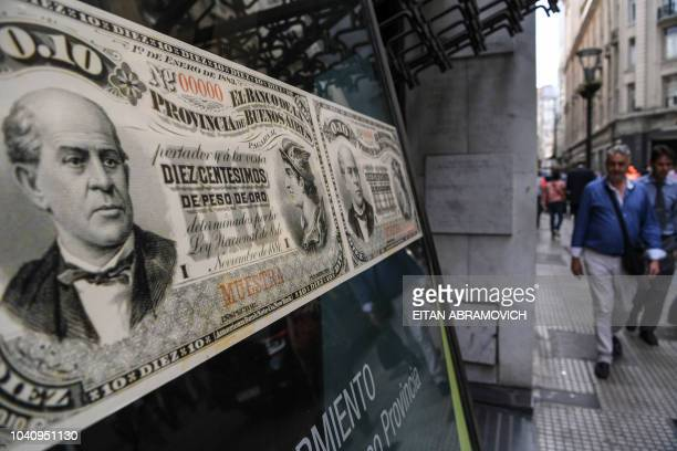 People walk past a bank's branch decorated with images of old Argentine peso bills in Buenos Aires on September 26 2018 A crisis of confidence...