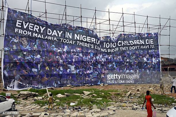 People walk past a banner displayed to campaign against malaria disease under the auspices of Moskeeto Armor a mosquito repellent fabric in Lagos on...