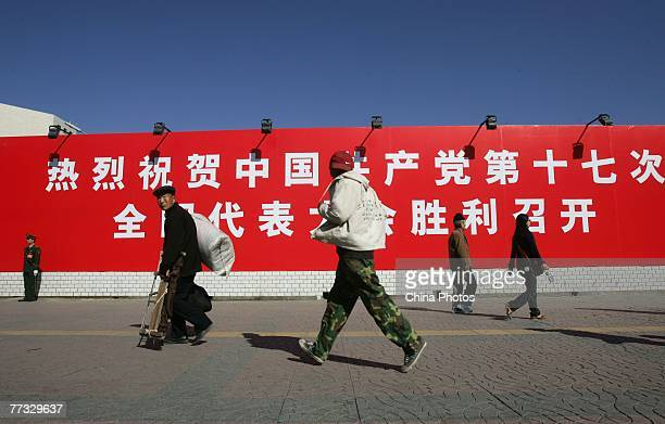 People walk past a banner marking the opening of 17th National Congress of the Communist Party of China , at the Xidan shopping area on October 15,...
