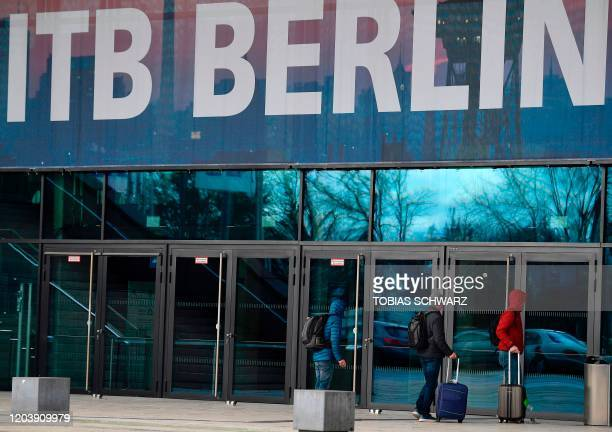 People walk past a banner promoting the International Travel Fair at the fair grounds in Berlin on February 28 2020 Authorities will decide on...