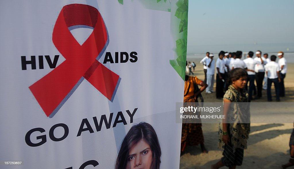 People walk past a banner with an AIDS awareness message at a rally on World AIDS Day in Mumbai on December 1, 2012. The UNAIDS agency says some 2.5 million Indians are living with HIV, many of them ostracised by their communities .