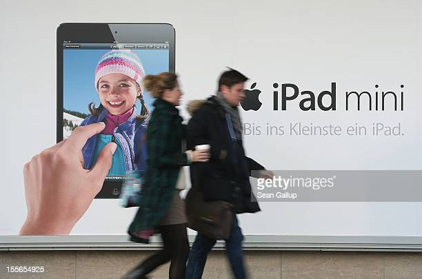 People walk past a billboard advertising the new Apple iPad mini on November 6 2012 in Berlin Germany Apple recently released the Mini to compete...