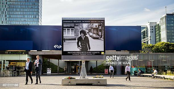 People walk past a billboard bearing a picture of late pop icon Michael Jackson during his visit to Amsterdam in 1977 made by Dutch photographer...