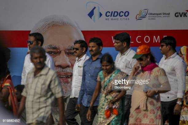 People walk past a billboard depicting Narendra Modi India's prime minister on display during a ceremony at the site of the new Navi Mumbai...