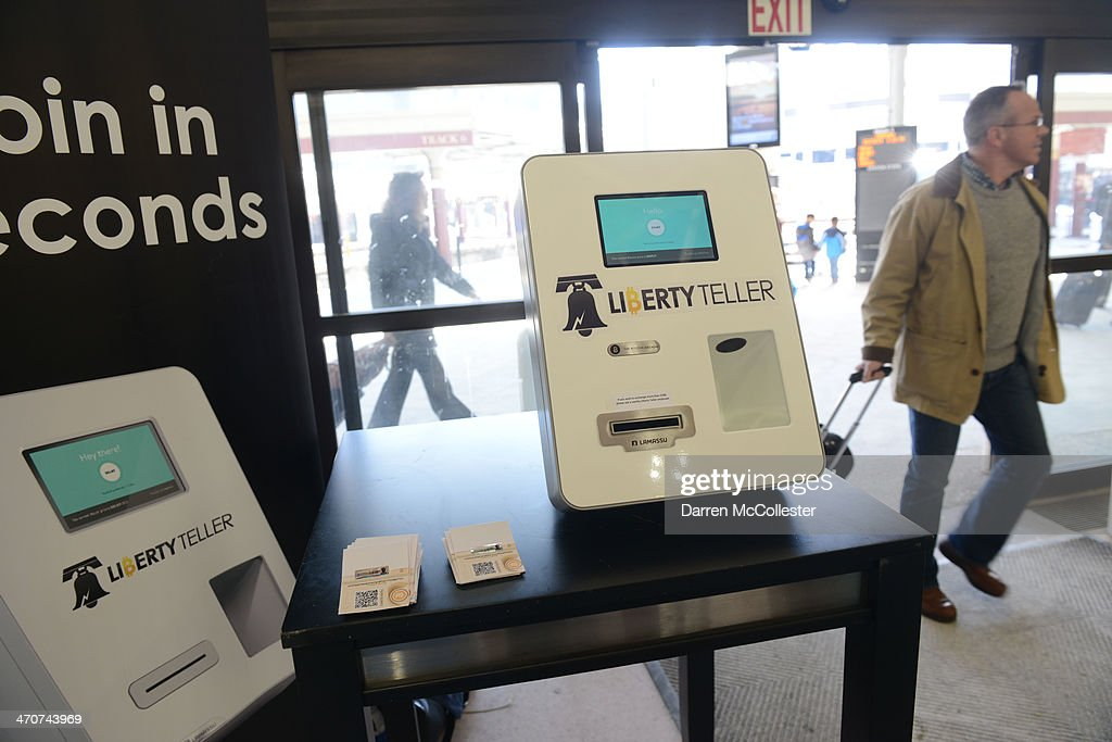 People walk past a Bitcoin ATM at South Station February 20, 2014 in Boston, Massachusetts. The ATM was placed by Liberty Teller to help inform people about the digital currency, which can be bought and sold anonymously, and can be used at a number of online retailers in place of cash or credit cards.
