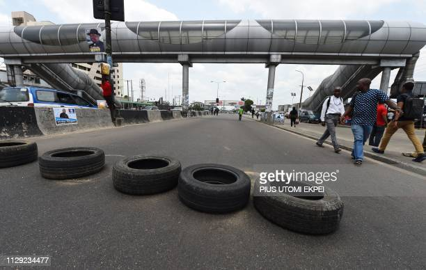 People walk past a blockade mounted with used tyres by soldiers on the road leading to the main gate of the Independent National Electoral Commission...