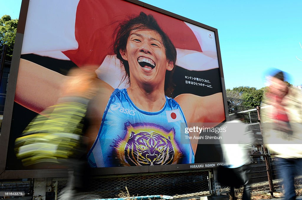 People walk past a board promoting 2020 Olympic Tokyo bid at Harajuku Station on February 13, 2013 in Tokyo, Japan. International Olympic Committee's decision to drop wrestling from 2020 Summer Olympic stuns Japan, as Japan won six medals in Wrestling including four gold at London Olympic.
