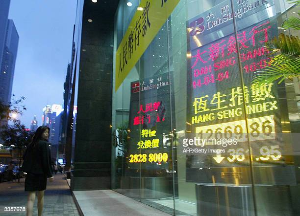 People walk past a board showing the key Hang Seng index in Hong Kong 14 April 2004. Hong Kong shares fell sharply lower on fears of US interest rate...