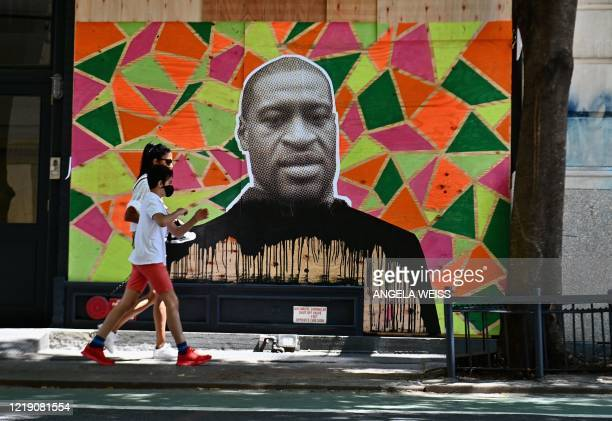 People walk past a boarded up store front with a George Floyd mural on June 10 2020 in New York City On May 25 Floyd a 46yearold black man suspected...
