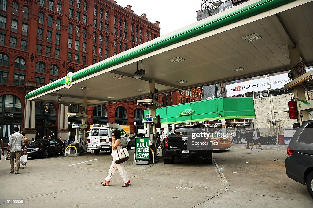 People walk past a BP gas station, one of the few remaining