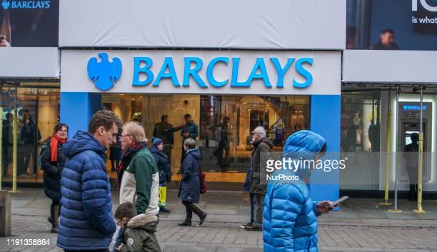 People walk past a branch Barclays Bank in Central Manchester.