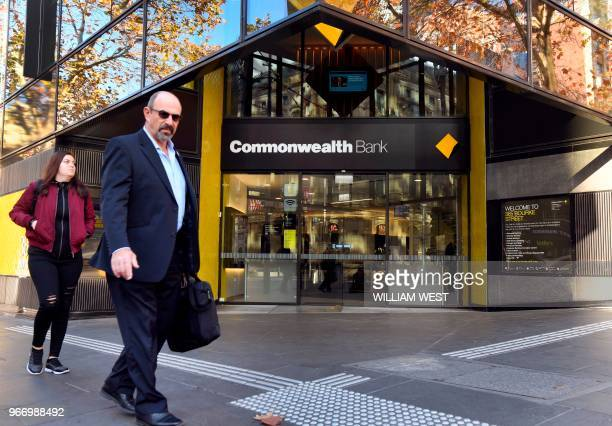 People walk past a branch of Australia's Commonwealth Bank in Melbourne on June 4 2018 The Commonwealth Bank on June 4 agreed to the largest civil...