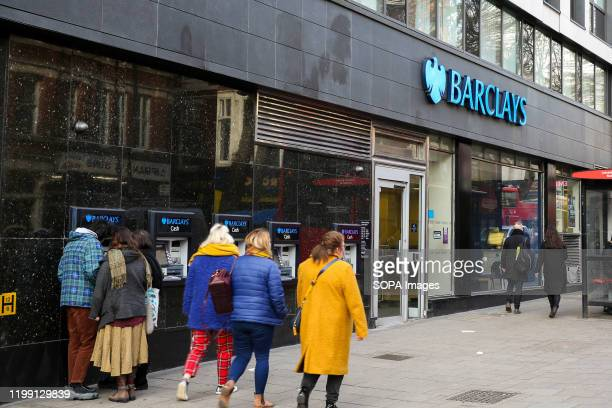 People walk past a branch of Barclays Bank in central London