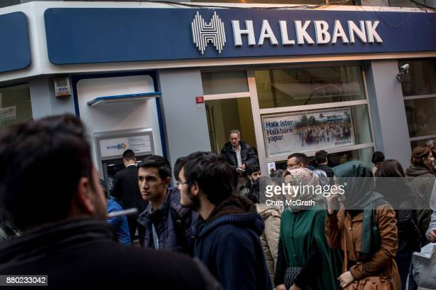 People walk past a branch of the Turkish Halk Bank on November 27 2017 in Istanbul Turkey The trial of Mr Reza Zarrab an IranianTurk who ran a...