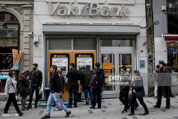 People walk past a branch of Turkish bank VakifBank on December 1 2017 in Istanbul Turkey The trial of Mr Reza Zarrab an IranianTurk who ran a...