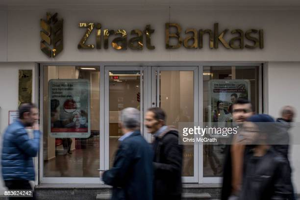 People walk past a branch of Turkish bank Ziraat Bank on December 1 2017 in Istanbul Turkey The trial of Mr Reza Zarrab an IranianTurk who ran a...