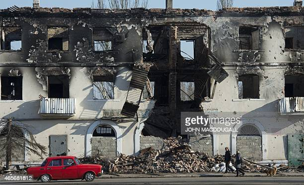 People walk past a building damaged in fighting in Vuhlehirsk, just south of Debaltseve March 9, 2015. The city, captured from Ukrainian troops by...