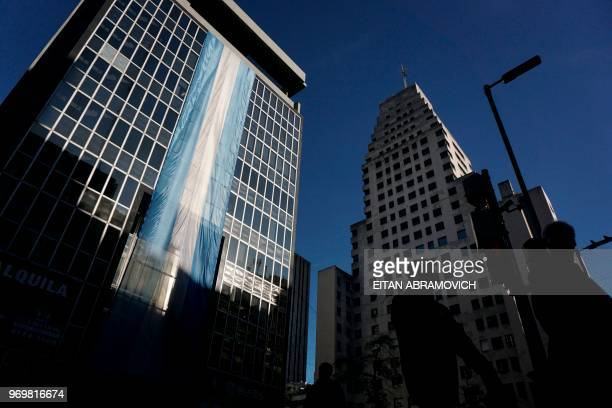 People walk past a building decorated with the Argentinian national flag in the financial district of Buenos Aires on June 08 2018 Argentinian peso...