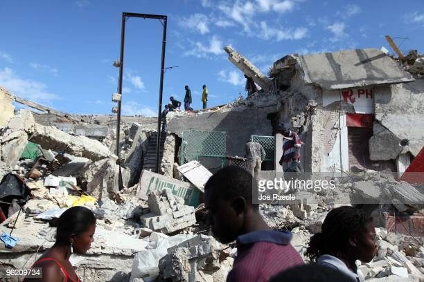People walk past a building that was destroyed during the massive earthquake on January 27 2010 in PortauPrince Haiti Planeloads of rescuers and...