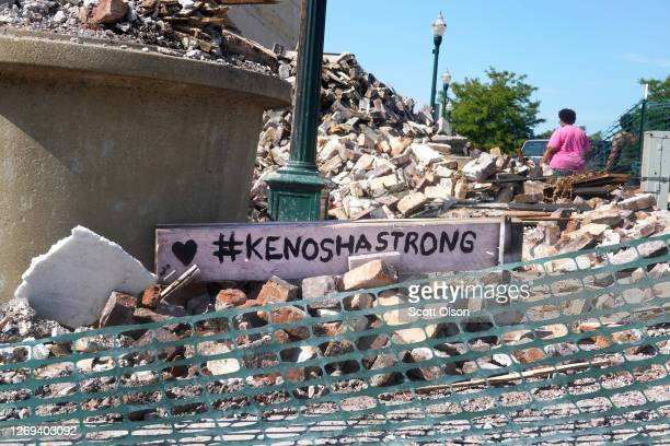 People walk past a building that was reduced to rubble after being burned during recent rioting following the shooting of Jacob Blake on August 28...